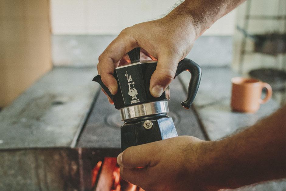 Homem segurando uma cafeteira Moka preta em frente a fogão de lenha.