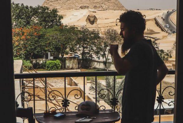 Imagem de um homem tomando café frente a pirâmide do Egito
