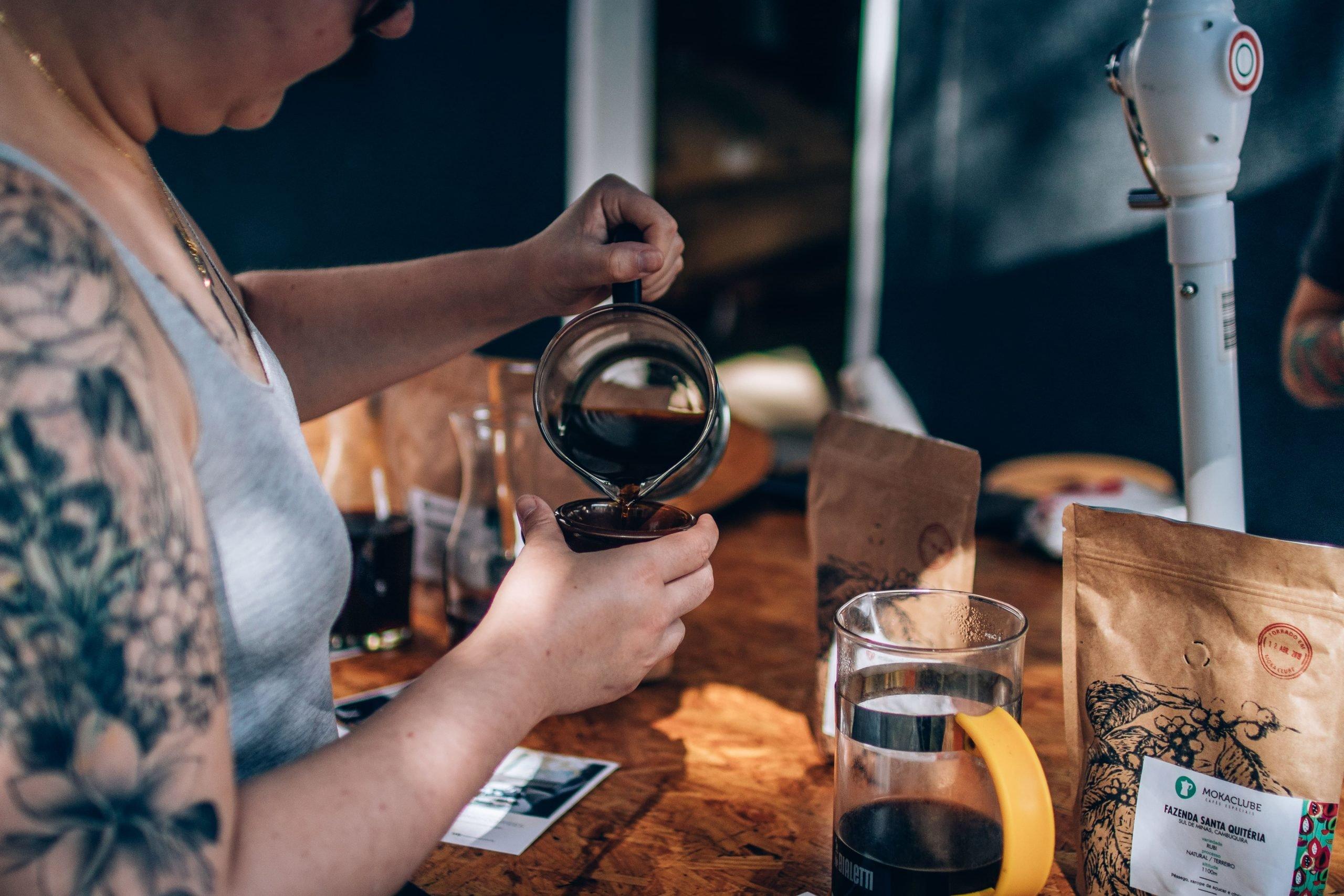 Mulher servindo café especial na xícara.