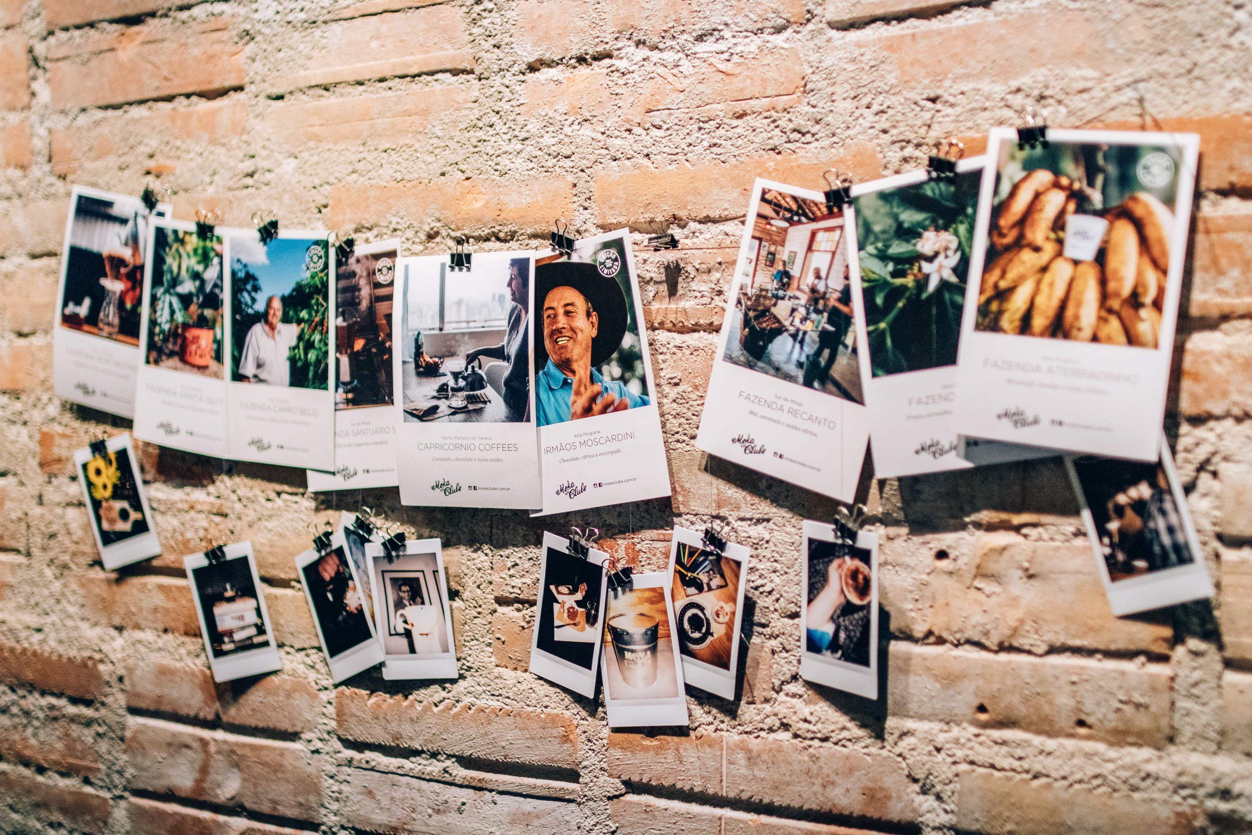 Imagens que acompanham os grãos do clube de assinatura de café do Moka pregadas à parede em cafeteria.
