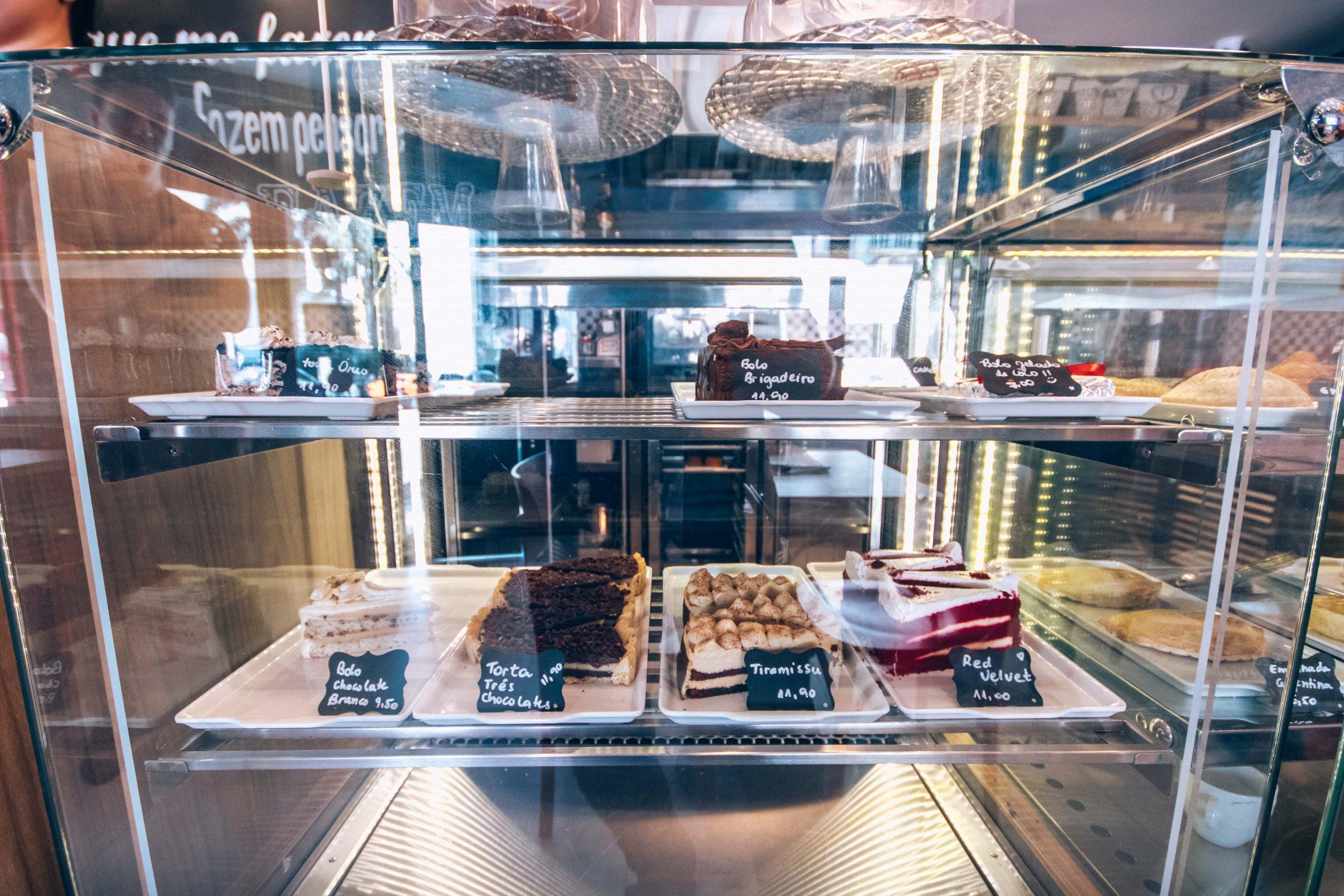 Vitrine com diversos bolos servidos, receitas doces com café que combinam com um pretão.
