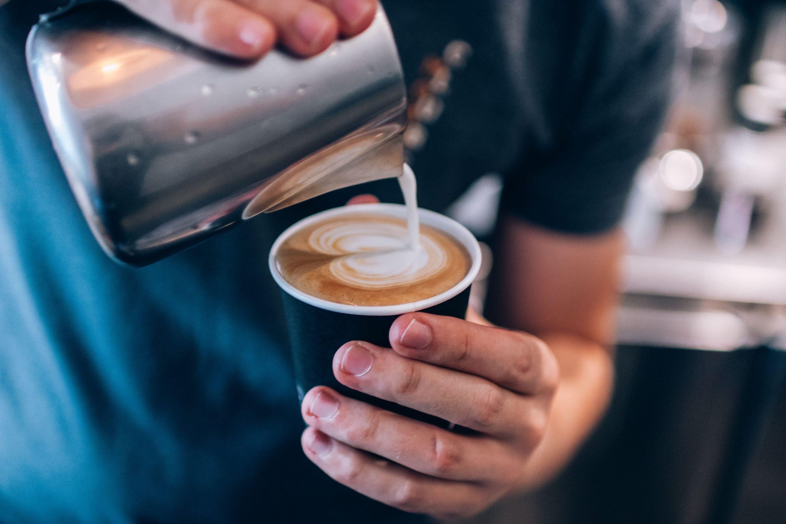 Café macchiato sendo servido na xícara.