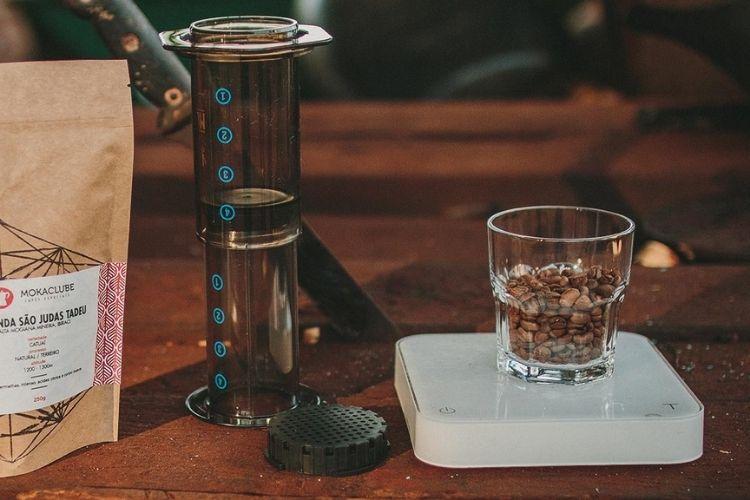 Cafeteira aeropress ao centro com um copo ao lado direito e um saco de café a esquerda.