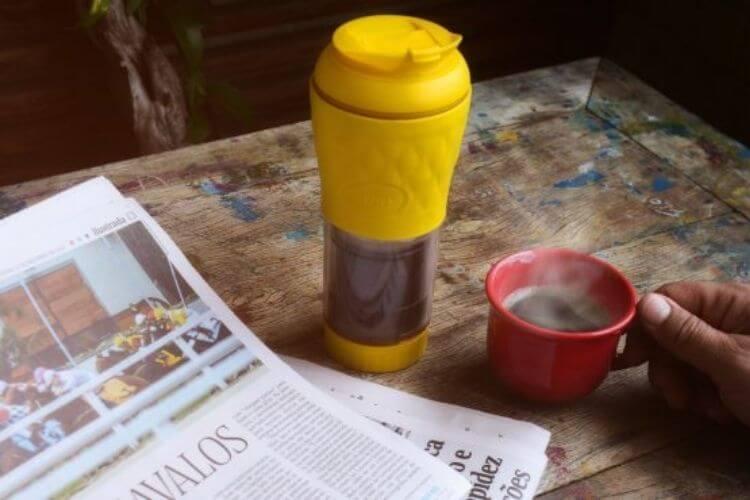 Cafeteira pressca amarela em cima de uma mesa com jornal aberto.
