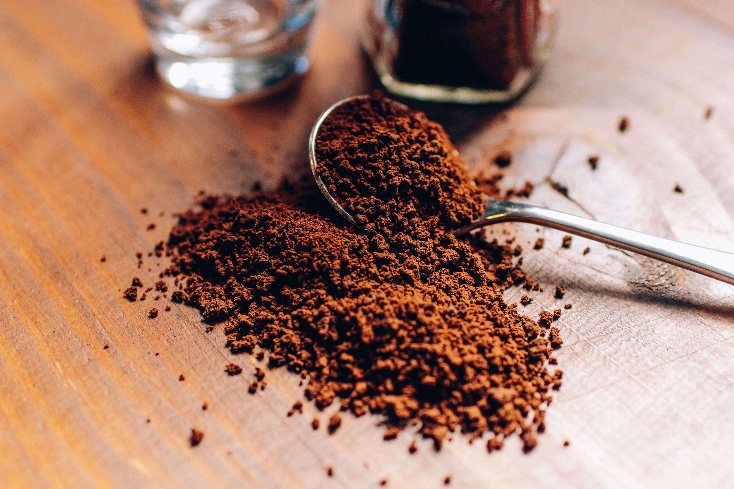 Pó de café na colher parar preparar um café coado em casa.