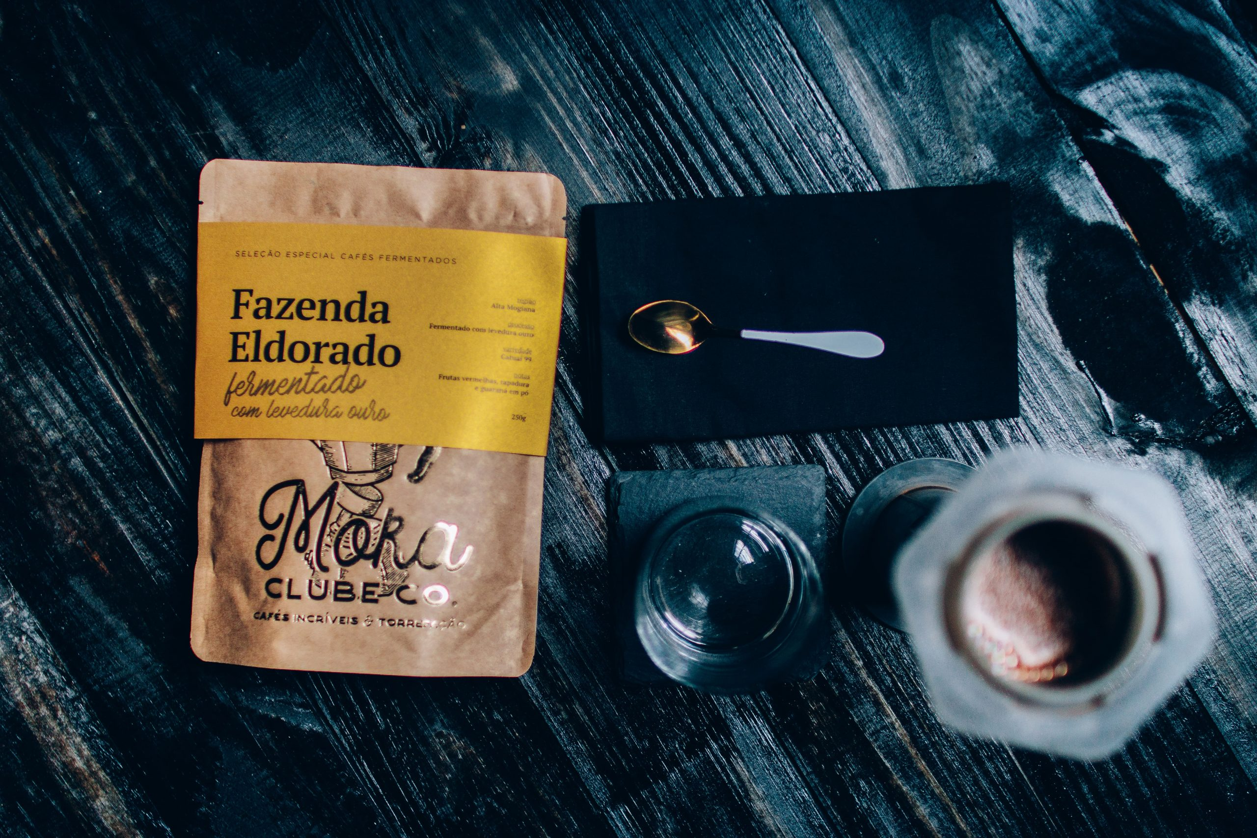 Tipo de grão de café da Fazenda Eldorado disponível no Moka. Rótulo amarelo e, ao lado, uma colher.
