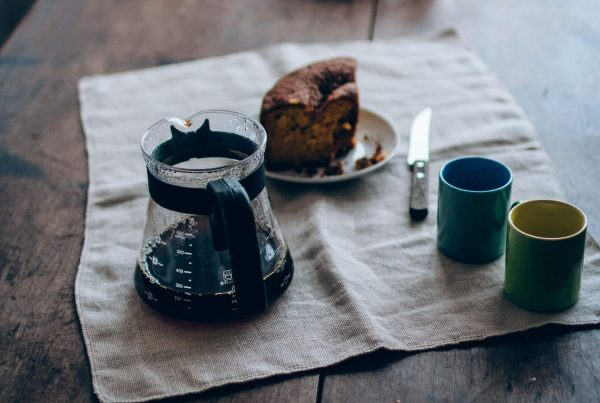 Mesa com um pedaço de bolo de chocolate, com uma xícara de café quase vazia e duas canecas coloridas.
