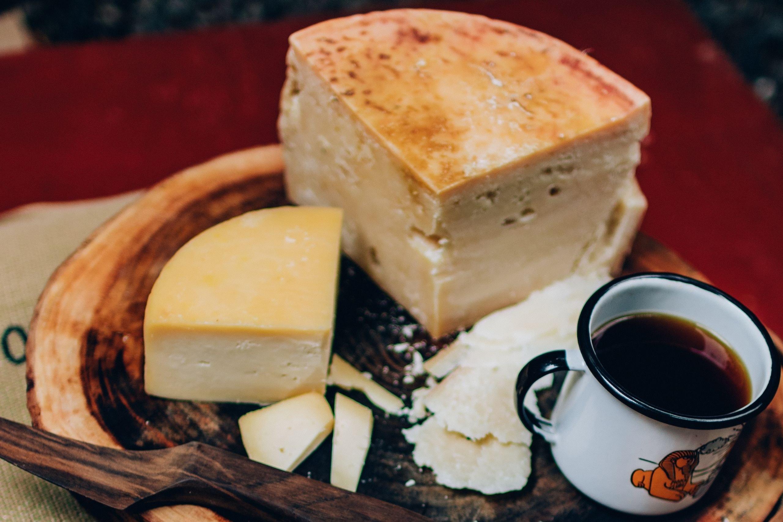 Mesa com queijo cortado aos pedaços e uma xícara cheia de café.