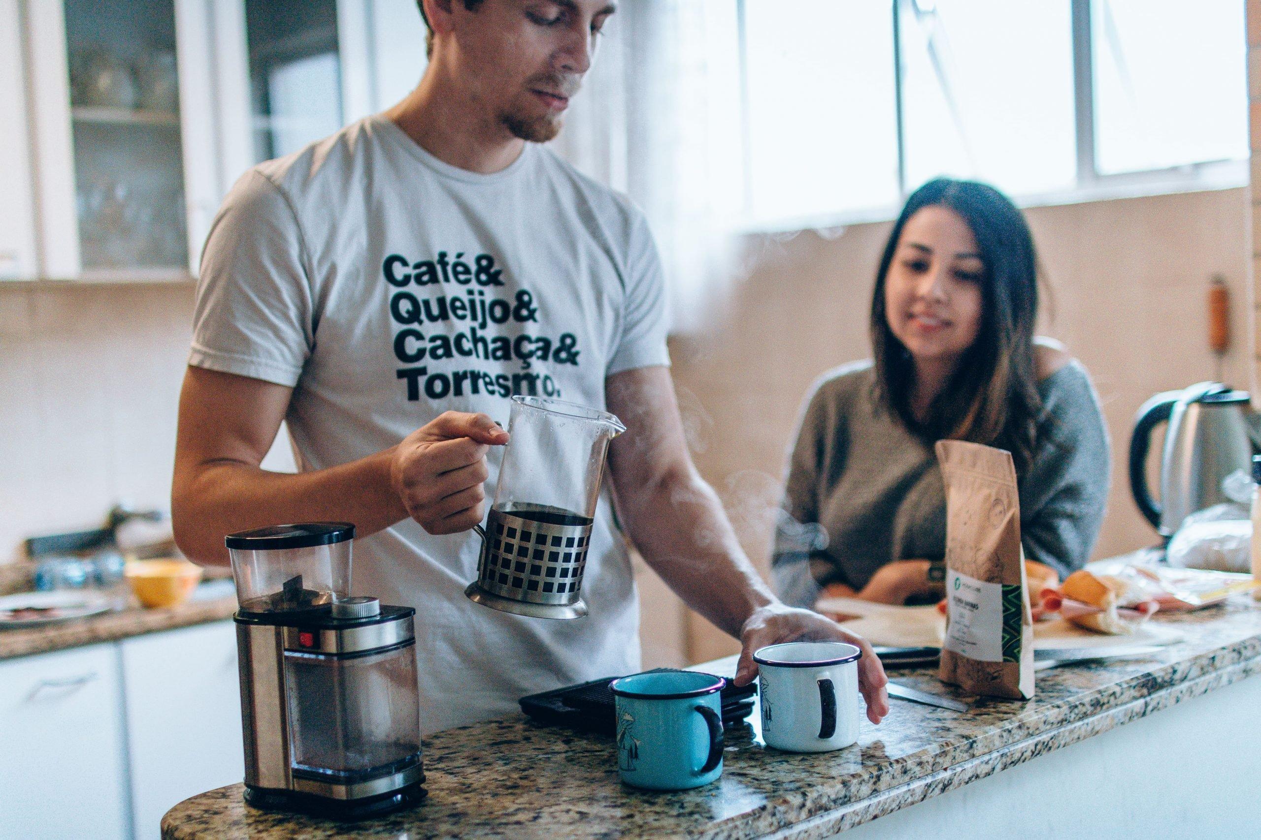 Homem e mulher na cozinha, preparando um café com o grão especial do Moka em uma prensa francesa.