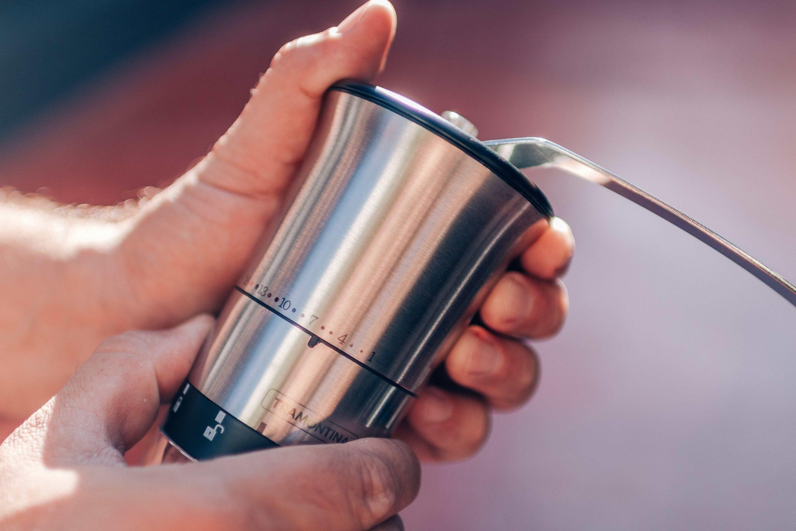 Moedor de café manual sendo utilizado para preparar café coado em casa.