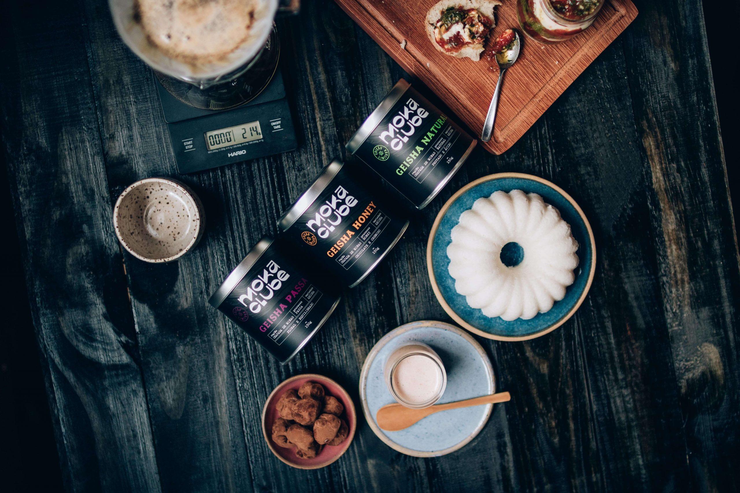 Diferentes cafés para prensa francesa expostos com pudim, bolachas e outros alimentos.