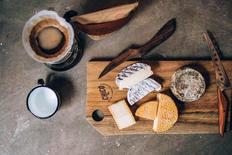 Tábua com queijos e uma xícara de café ao lado.