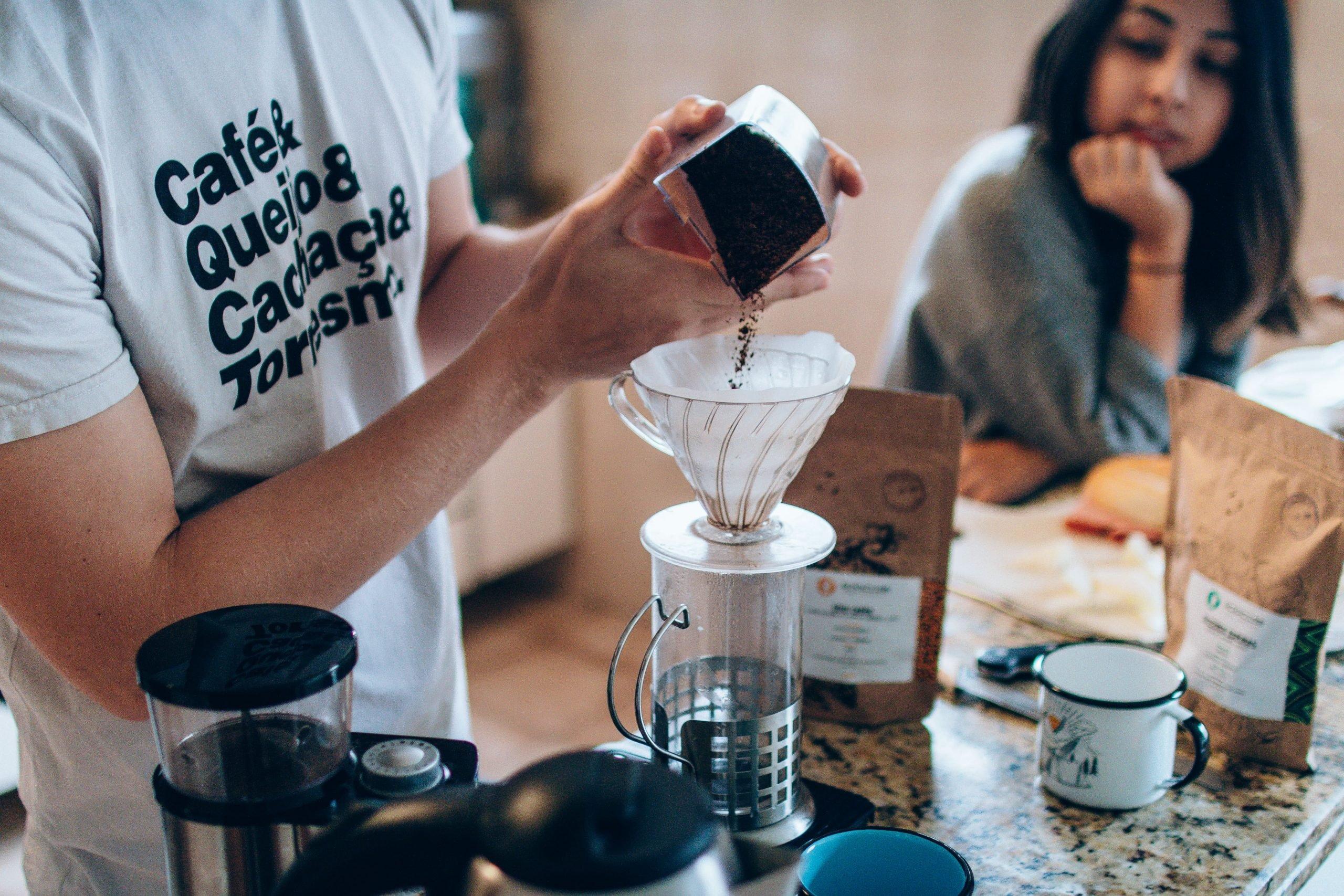 Homem preparando um café cremoso com leite chocolate em pó.