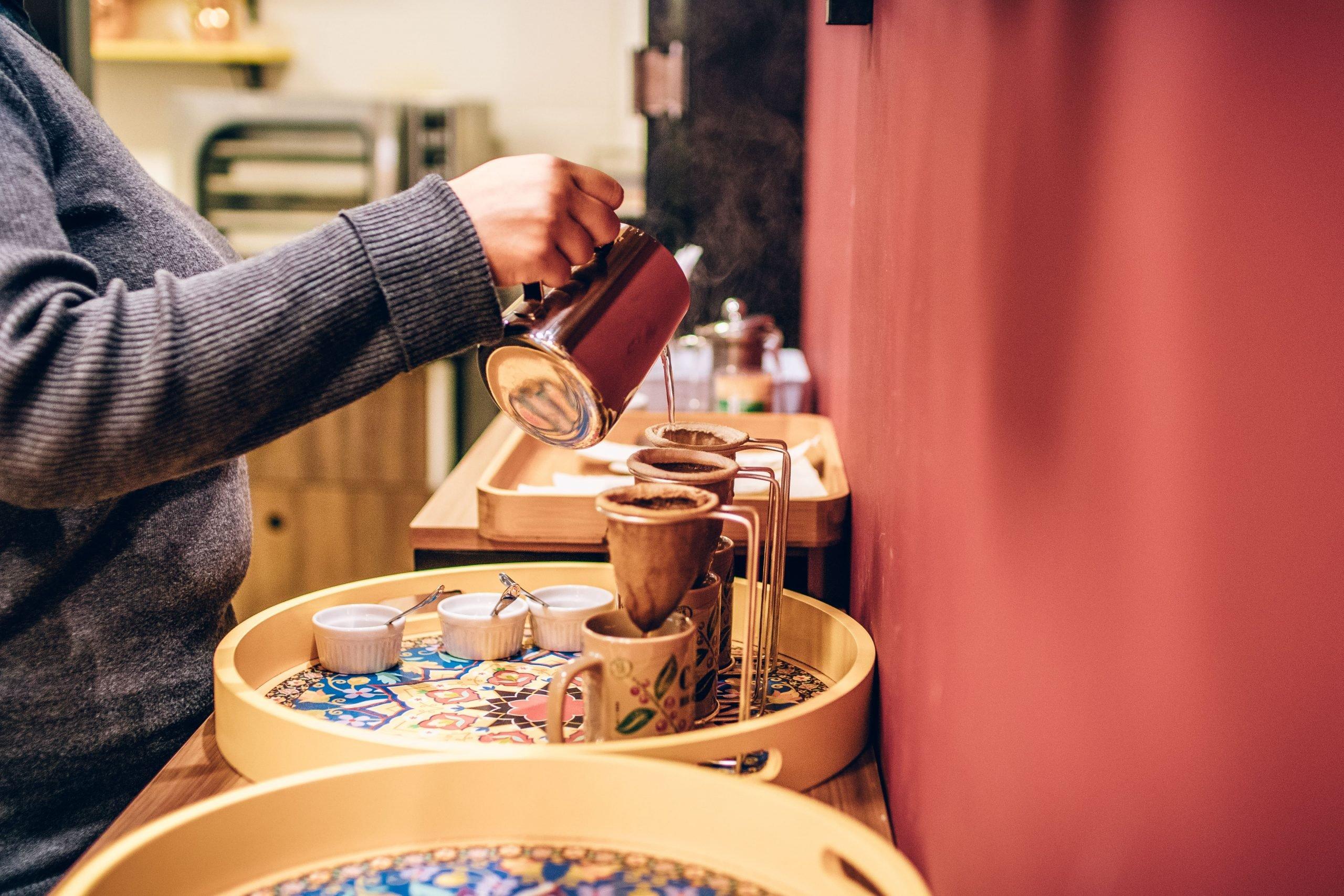 Pessoa pegando água quente para fazer café de qualidade.