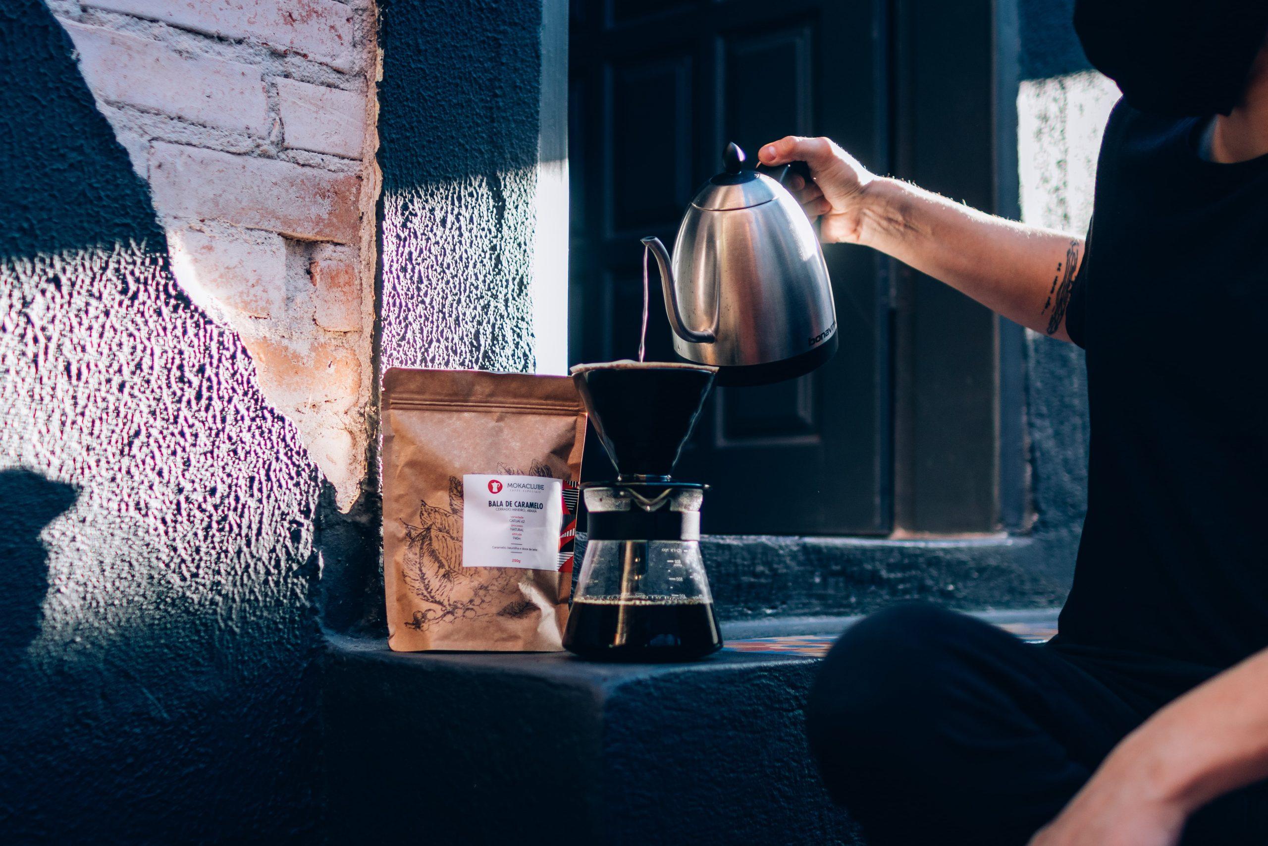 Pessoa com saco para armazenar café ao lado da chaleira, preparando a bebida.