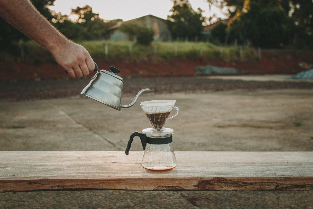Pessoa utilizando equipamentos para fazer café para passar a bebida.