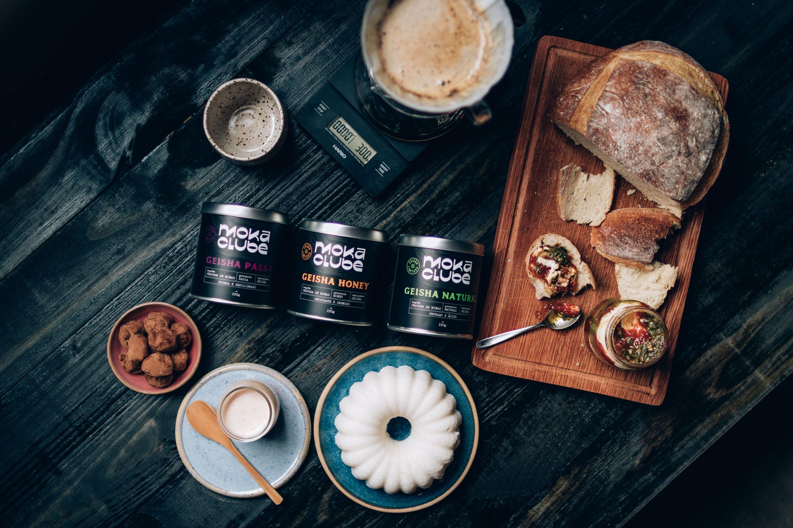 Cafés do Moka Clube em suas embalagens para armazenar o grão, disposta na mesa com pães e doces.