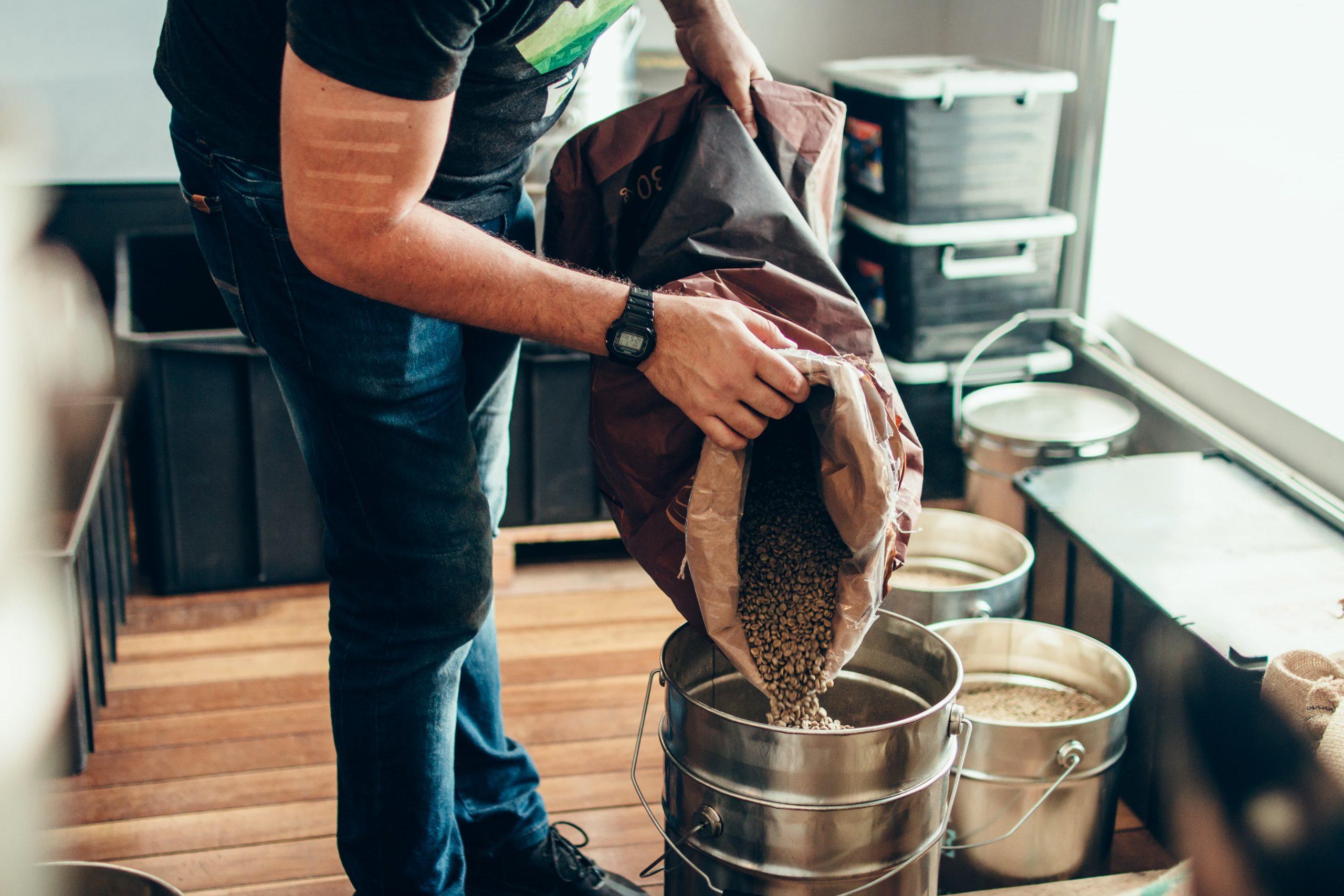 Homem despejando grão de café em lata de metal com alça.