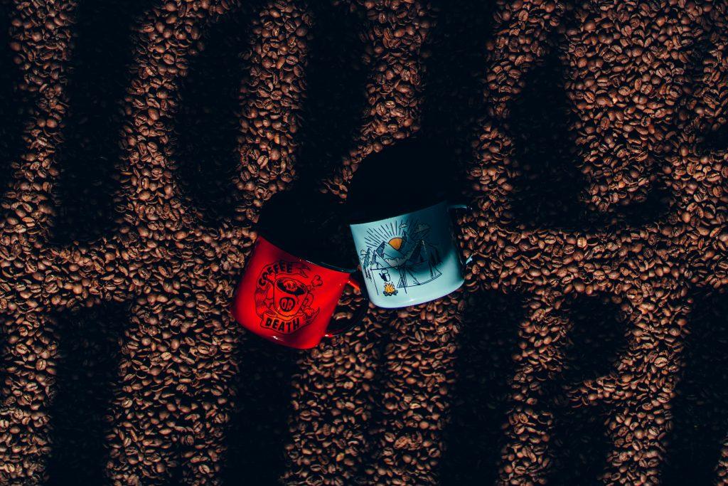 Canecas colocadas sobre grãos de café com a escrita Moka Clube sobre eles em uma espécie de sombra,