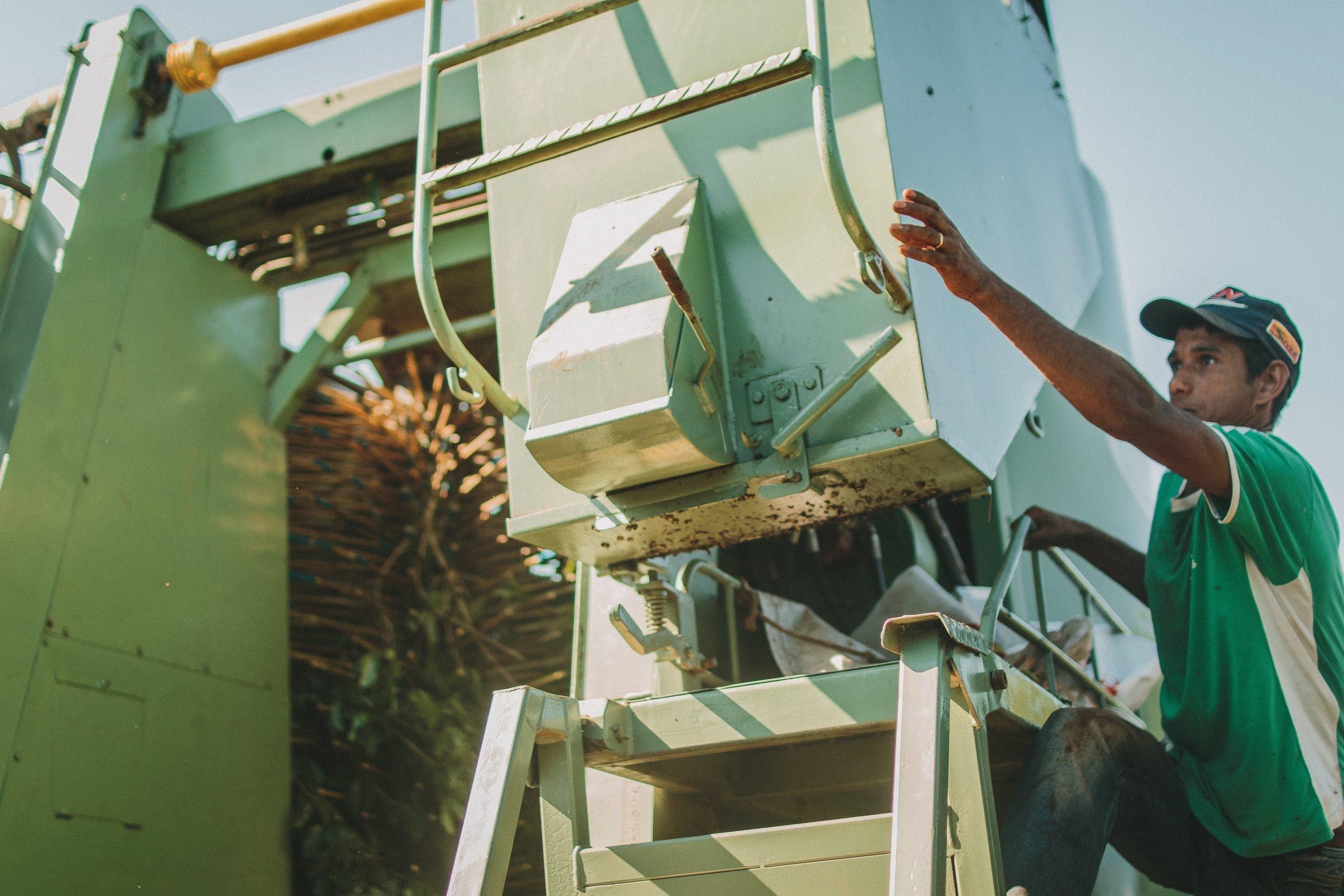 Homem manuseando máquina agrícola que colhe os grãos de café.