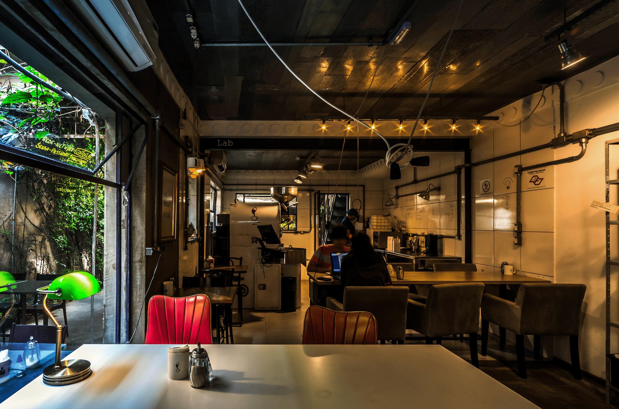 Estabelecimento do Coffee Lab vazio, com iluminação amarela, mesas brancas e cadeiras com almofadas vermelhas.