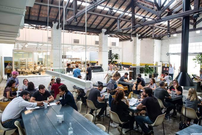 Cafeteria Futuro Refeitório em horário de pico, com mesas de madeira e cadeiras de plástico ocupadas por diversas pessoas.