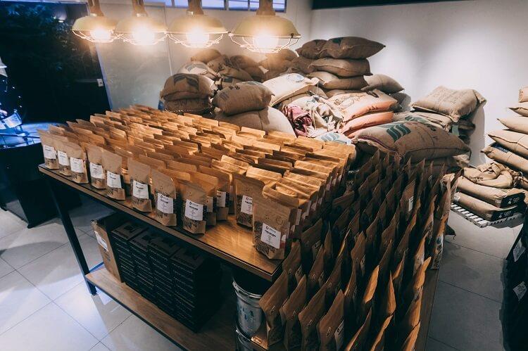 Saca cheia de sacos de café. No centro uma mesa com vários pacotes de café individuais.