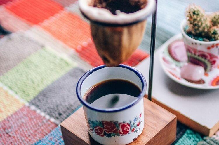 Coador de café de pano com xícara embaixo.