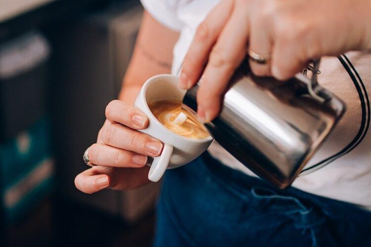 Mulher fazendo art latte no café.