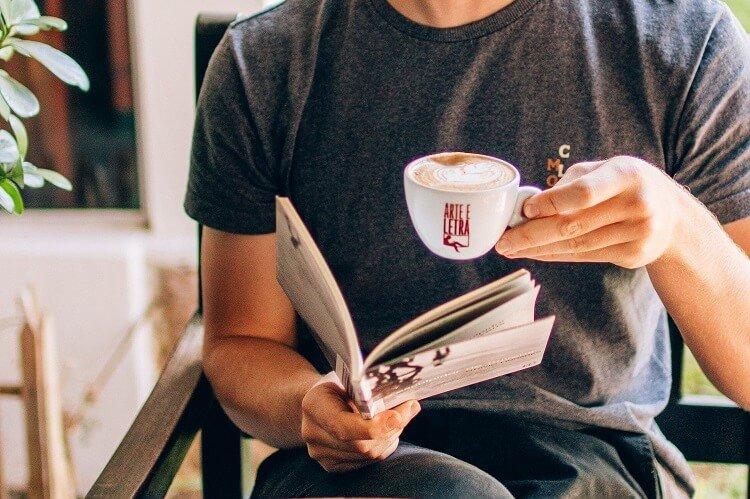 Homem lendo com uma xícara de café na mão.