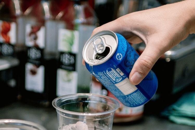 Homem colocando água tônica em um copo