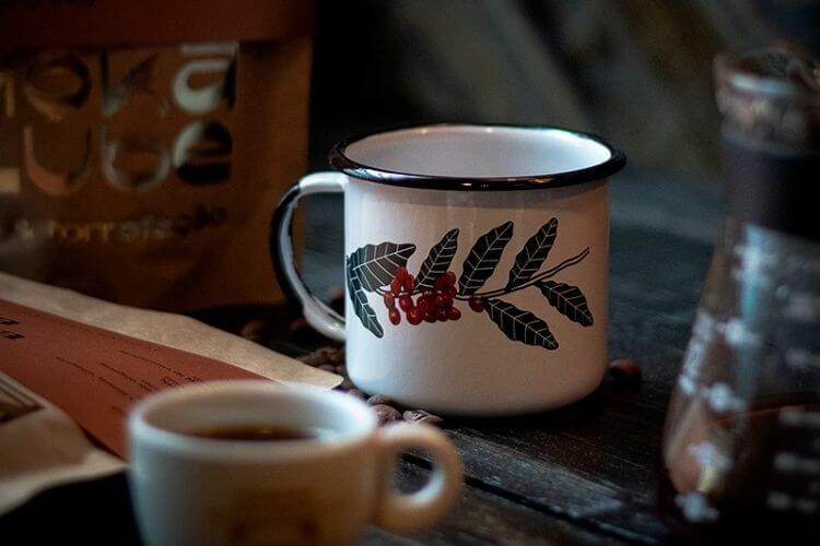 Caneca de café branca com uma folha e grãos decorados no meio