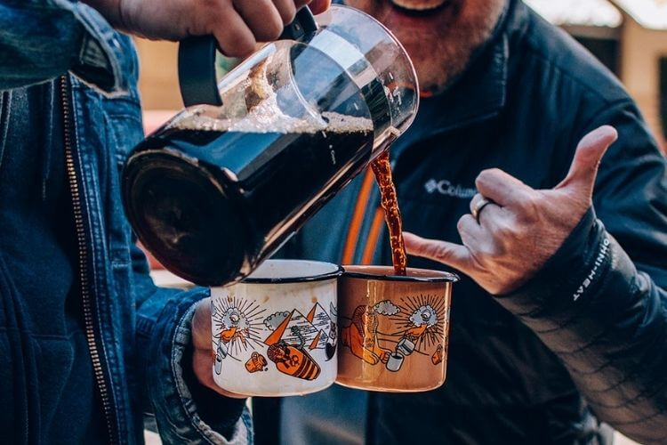Homem segurando duas canecas, uma branca e outra laranja, colocando café nelas