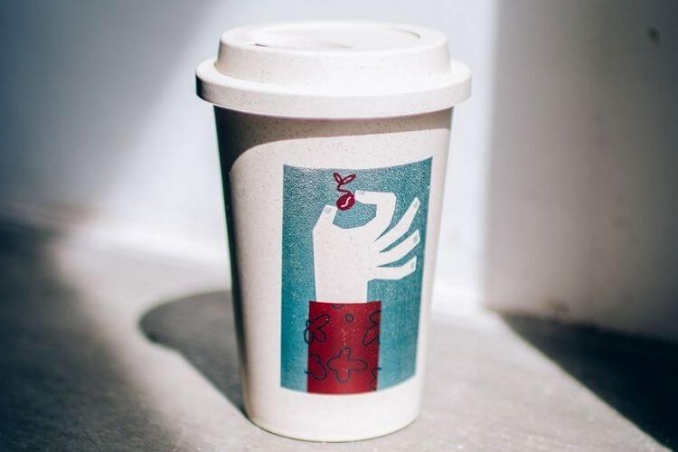 copo reutilizável para café branco com imagem verde água no meio.