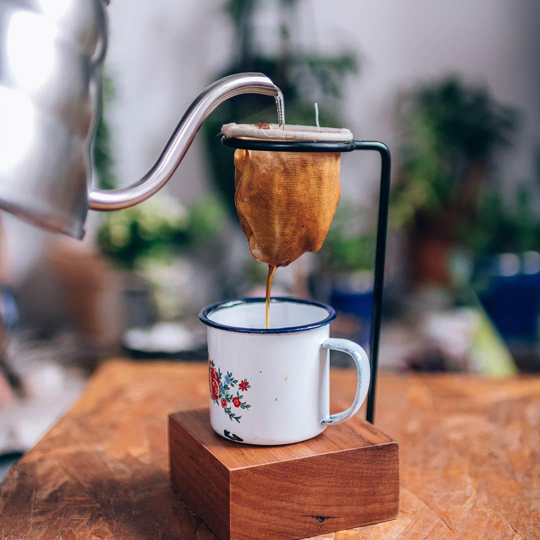 Coador de pano coando café em uma caneca branca