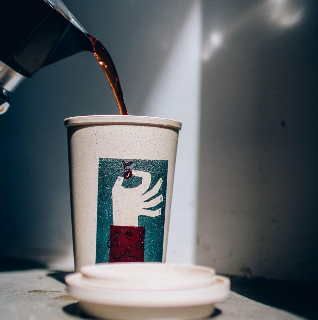 Copo retornável com tampa aberta e café sendo servido