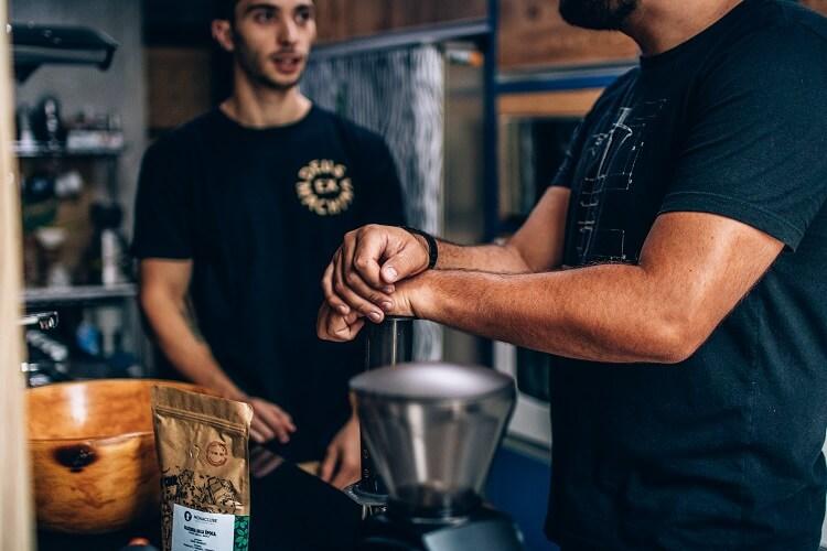 Dois homens conversando e fazendo café