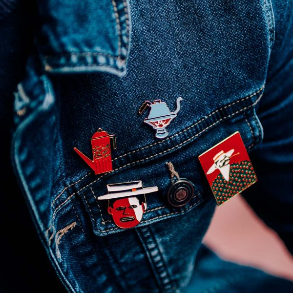Quatro pins em uma jaqueta jeans