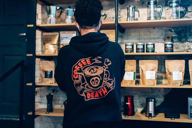 Homem com moletom mexendo em uma prateleira de café