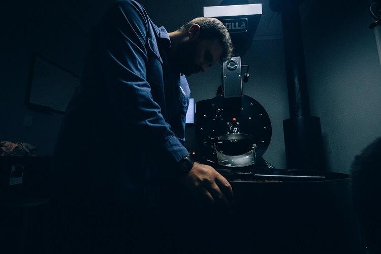 Homem mexendo com grãos de café