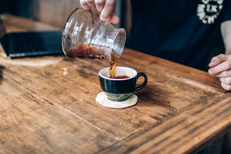 Homem servindo café em uma xícara preta