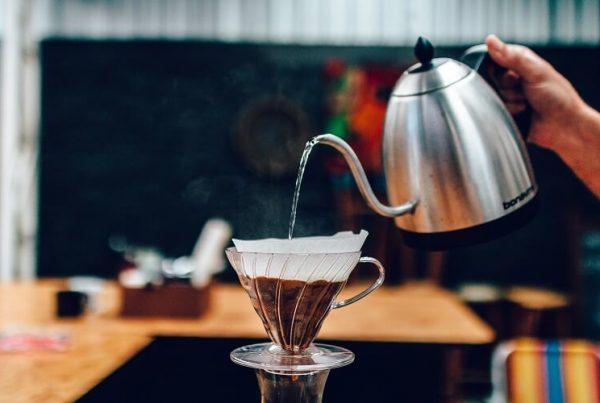Chaleira despejando água para coar café